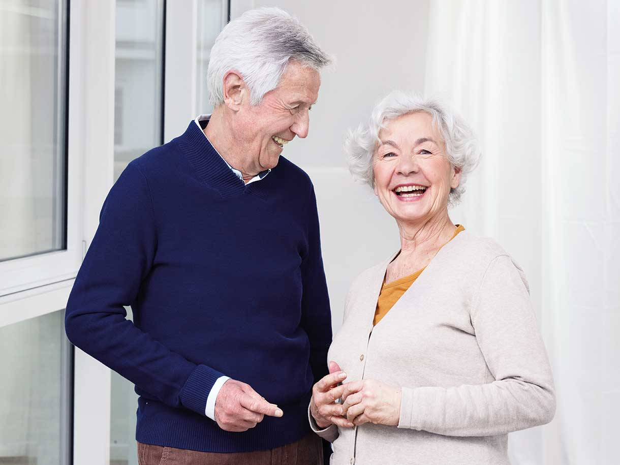 An older man and older woman standing together smiling
